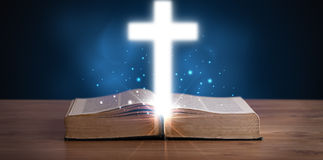Open holy bible with glowing cross in the middle Royalty Free Stock Photos