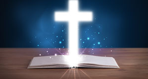 Open holy bible with glowing cross in the middle Royalty Free Stock Photo