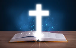 Open holy bible with glowing cross Stock Photography
