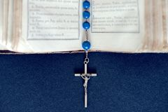 Open Holy Bible with silver cross. Blue Christian cross necklace on open Holy Bible Royalty Free Stock Photography