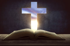 Open holy bible with wooden cross in the middle Royalty Free Stock Image