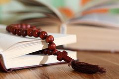 Open holy bible with wooden cross in the middle. Christian concept Stock Photos