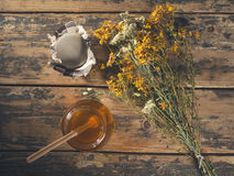 Open honey jar with drained flowers Royalty Free Stock Photo