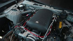 Open hood black sports car for street racing drift, inside running engine. Motor, outside in the afternoon, close-up, slow motion stock video