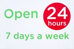 Open 24 hours 7 days a week round circle sign red and green against white background for shop opening times stock image