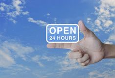 Open 24 hours icon on finger. Over blue sky, Business full time service concept stock photo