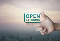 Open 24 hours icon on finger over city tower. At sunset, vintage style Stock Image