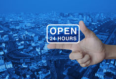 Open 24 hours icon on finger. Over modern city tower, street and expressway, Business full time service concept Stock Photo