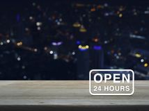 Open 24 hours icon on wooden table over blur colourful night lig. Ht city tower background Royalty Free Stock Photo