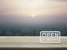 Open 24 hours icon on wooden table. Over city tower at sunset, vintage style Royalty Free Stock Photo