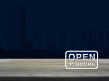 Open 24 hours icon on wooden table over modern office city tower. Blue tone background Stock Images