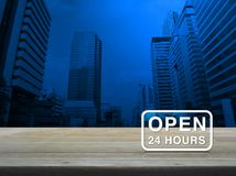 Open 24 hours icon on wooden table over modern office city tower. Blue tone background Stock Photos