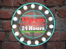 Open 24 hours neon text sing on brick wall business background  Royalty Free Stock Image