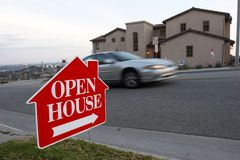 Open house sign. Red and white open house sign with a car passing by and the house in the background Stock Image