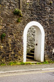 Open houten deur met gerichte gotische boog op een witte steenmuur royalty-vrije stock fotografie