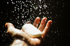 Open human hand with soap under water drops. Photograph of an open human hand with soap under water drops Stock Image