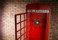 Open iconic red British telephone booth. Open wooden replica of an iconic red British telephone booth with a vintage dial-up telephone, sign and crown against a Stock Photography