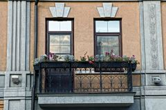 Open iron balcony with floral balconies on the wall of the house with windows Stock Photo