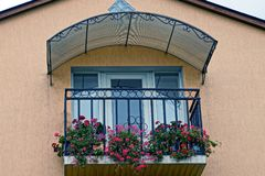 Iron balcony with flowerpots with decorative flowers on the wall of the house with windows and doors Stock Photos