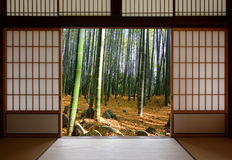 Open Japanese sliding doors and lush green bamboo forest stock image