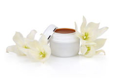 Open jar with the cosmetic cream and flowers Stock Photography