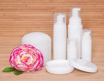 Open jar of cream and other body care cosmetics with a flower Stock Image