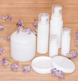 Open jar of cream and other body care cosmetics with flowers Stock Photos