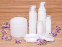 Open jar of cream and other body care cosmetics with flowers. On wooden background stock image