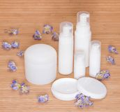 Open jar of cream and other body care cosmetics with flowers Royalty Free Stock Photography