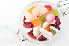 Open jar full of candies. Open glass jar full of different colourful jelly candies on white wooden background Royalty Free Stock Photo