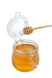 Open jar of honey and drizzler on white Stock Photos