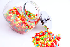 Open jar of jelly beans. Horizontal view of clear open jar and small pile of colorful jelly beans Royalty Free Stock Images