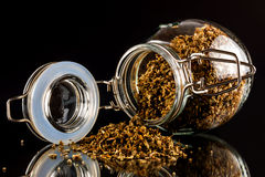 Open jar of oregano Royalty Free Stock Image