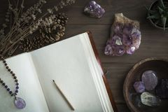 Open Journal or Notebook Surrounded by Amethyst Crystals Dried Lavender and Succulent Plant. Open leatherbound journal or notebook surrounded by amethyst stock photography