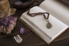 Open Journal or Notebook Surrounded by Crystals on a Wooden Surface. Open leatherbound journal or notebook surrounded by crystals on a wooden surface stock images