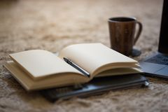 An open journal with pen and warm light illuminating blank pages. Coffee mug and laptop in background stock image
