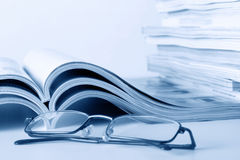 Open journals with glasses. In front Royalty Free Stock Photo