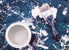 Open kan av vit målarfärg med borsten på blå träbakgrund Royaltyfria Bilder