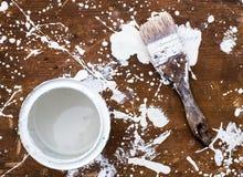 Open kan av vit målarfärg med borsten på träbakgrund Royaltyfria Bilder