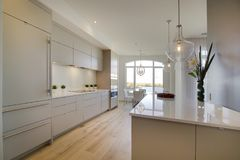 Open kitchen island with white acrylic doors. And white counter top Royalty Free Stock Photos