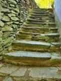 Open kleine stappen bij de oude bouw, oude uitgeputte steenachtige stappen achter huis Steenachtige muur van ruwe keien Stock Foto
