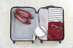 Open koffer met vrouwelijke kleding, schoenen stock afbeelding