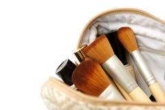 Open kosmetische zak met make-upborstels en een reeks schoonheidsmiddelen Stock Foto's