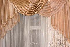 Open lambrequin (portiere, curtain) golden color on the window. Stock Images