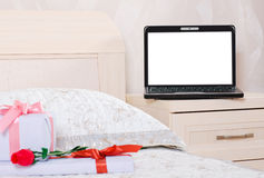 Open laptop with a blank screen is on the nightstand in the bedr. Oom and in front of him on the bed lay a flower and gift boxes Stock Photos