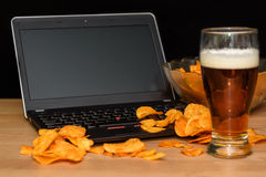 Open laptop with chips scattered on keyboard isolated on black b Royalty Free Stock Image