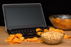 Open laptop with chips scattered on keyboard isolated on black b Royalty Free Stock Images