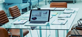 Open laptop computer with financial charts and papers spread out on the desktop before starting business negotiations. The photo is a blank space for your text Royalty Free Stock Image