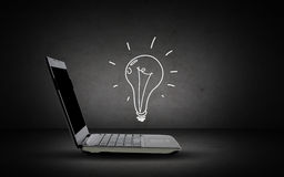 Open laptop computer with lighting bulb doodle Stock Photos