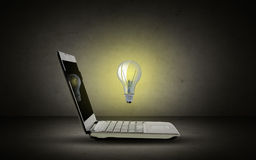 Open laptop computer with lighting bulb Royalty Free Stock Images